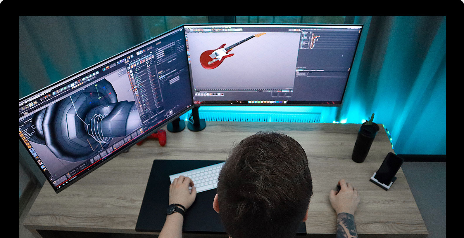 Man sitting in front of workstation with 3d model of a guitar